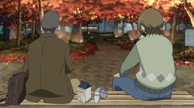 紅葉の下のベンチでおにぎりを食べる矢三郎と淀川教授