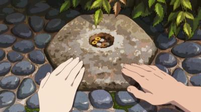 へそ石様に手を置く矢一郎と早雲